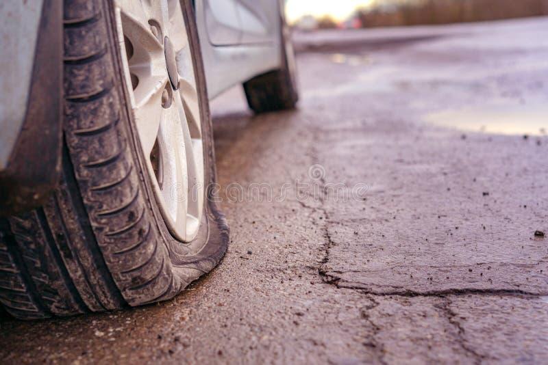 pneu plat sur la route Fuite de pneu de voiture en raison du broyage de clou toned image stock