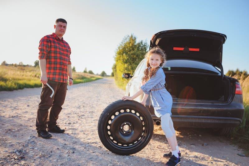 Pneu quebrado em mudança do pai e da filha durante a viagem por estrada rural do verão foto de stock