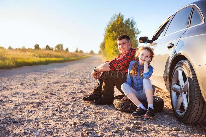 Pneu quebrado em mudança do pai e da filha durante a viagem por estrada rural do verão fotos de stock