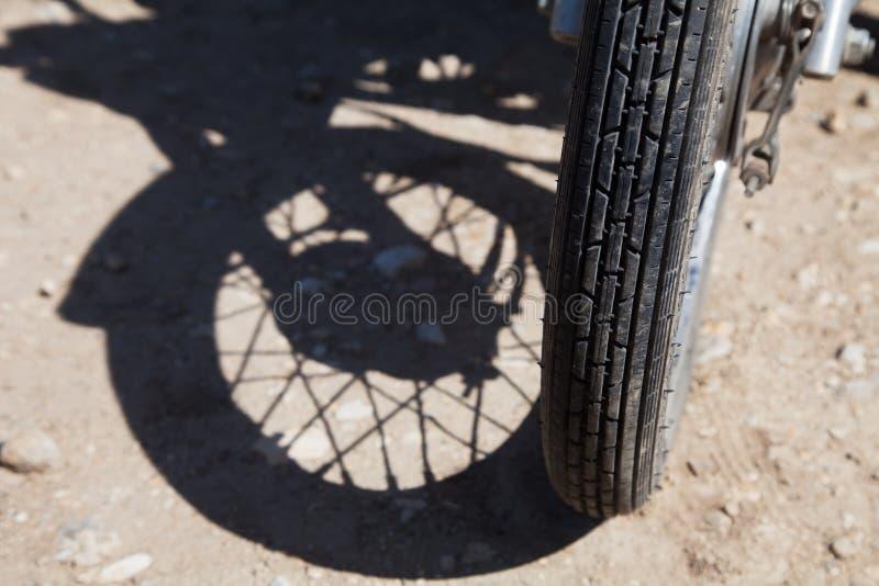 Pneumático de uma motocicleta e de sua sombra foto de stock
