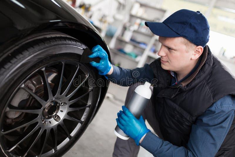 Pneumáticos de lavagem do carro do homem foto de stock