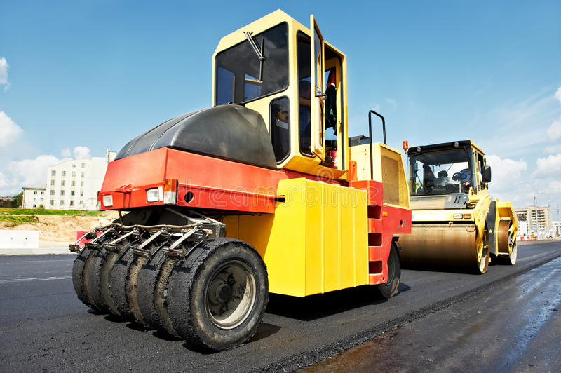 Pneumatic asphalt roller at work. Pneumatic tyred roller compactor at asphalt pavement works for road repairing royalty free stock image