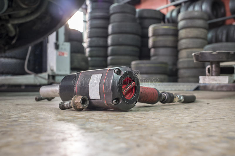 Pneumatic wrench screwing with no wheel car at bottom. Pneumatic wrench screwing mechanic tool and knots with no wheel car at bottom stock image