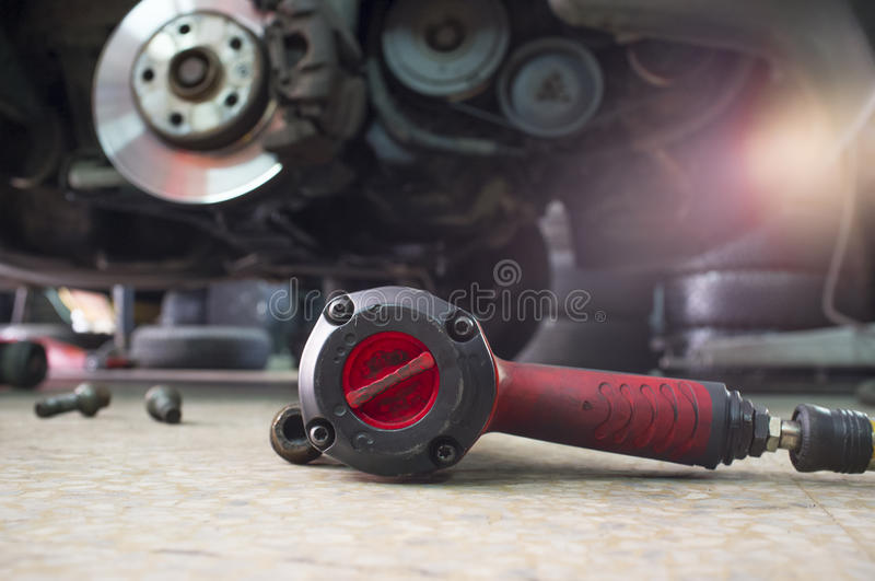 Pneumatic wrench screwing with no wheel car at bottom. Pneumatic wrench screwing mechanic tool and knots with no wheel car at bottom royalty free stock photos