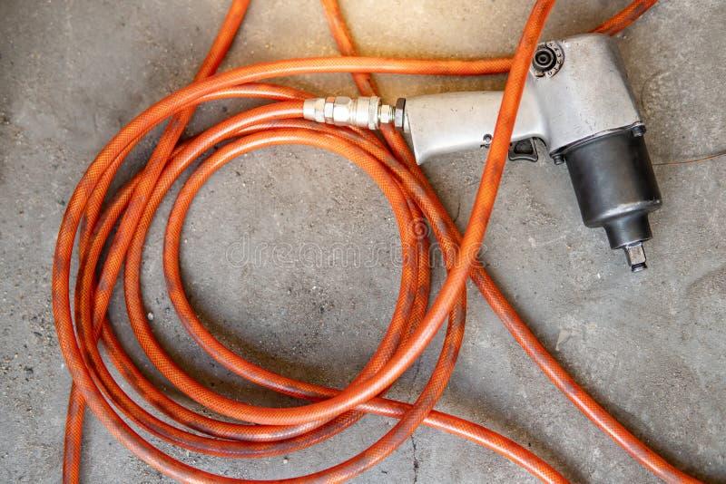 Pneumatisk skiftnyckel med slangröret på golvet royaltyfri fotografi