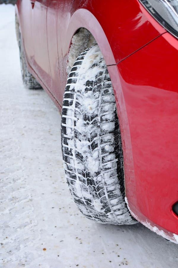 Pneus d'hiver, voiture rouge, route enneigée vide image libre de droits