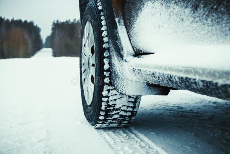Pneus de carro cobertos com a neve na estrada do inverno imagem de stock