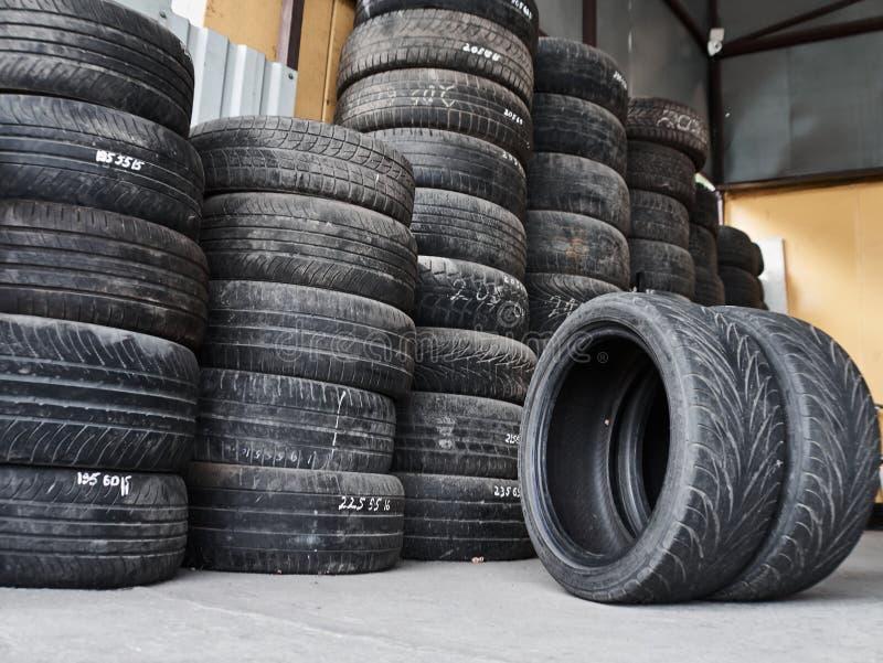 Pneus de carro usado empilhados nas pilhas em serviço apropriado do pneu Rodas para a oficina de reparações Concepr do serviço do imagem de stock royalty free