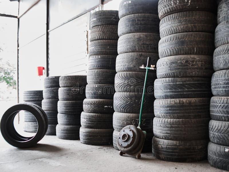 Pneus de voiture d'occasion empilés dans les piles à l'entrepôt de ferraille Vieilles roues réutilisant et concepr d'utilisation photo libre de droits