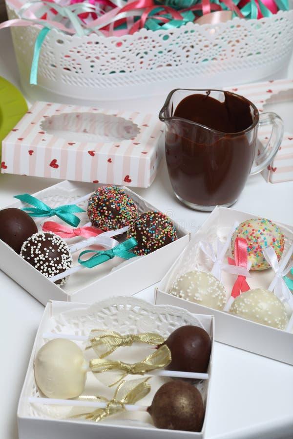 PNF do bolo decorados com uma curva da tran?a, embalada em uma caixa de presente Estão próximo os copos com chocolate derretido e imagens de stock