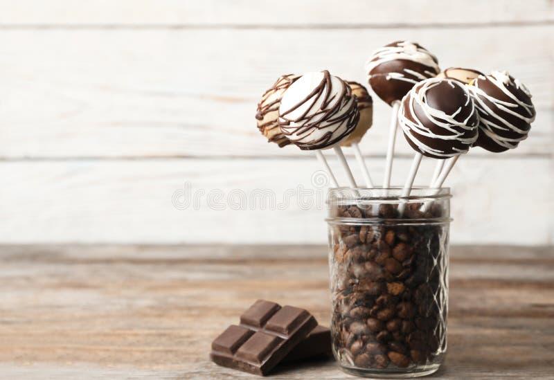 PNF saborosos do bolo revestidos com o chocolate no frasco de vidro completamente de feij?es de caf? na tabela imagens de stock
