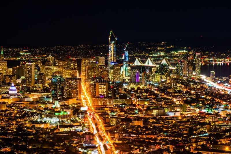 Pnoramic sikt för natt av det San Francisco centret med skyskrapor och den Okeland bron royaltyfri fotografi