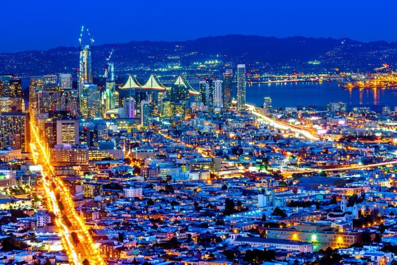 Pnoramic sikt för natt av det San Francisco centret med skyskrapor och den Okeland bron royaltyfria foton