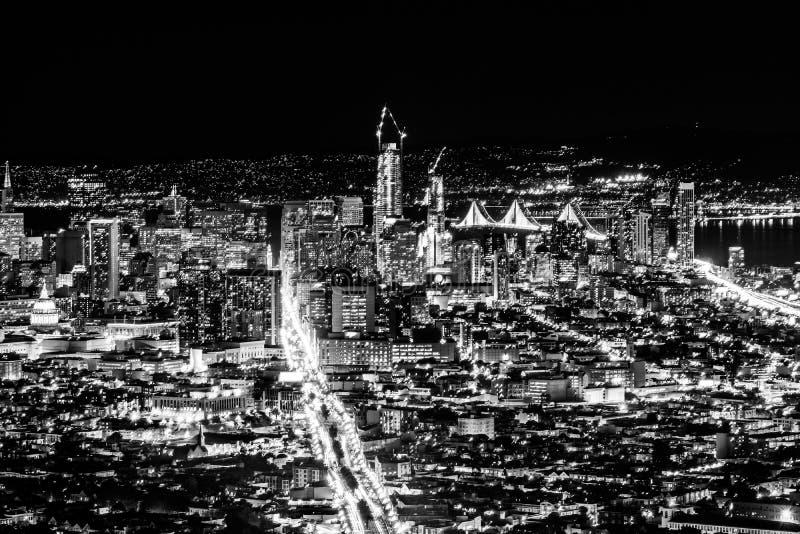 Pnoramic sikt för svartvit natt av det San Francisco centret med skyskrapor och den Okeland bron fotografering för bildbyråer