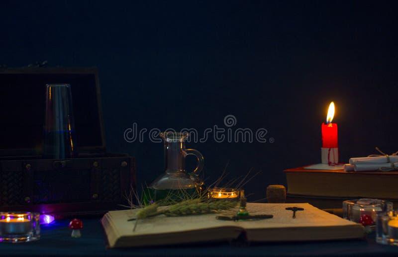 Poção mágica, livros antigos e velas no fundo escuro foto de stock royalty free