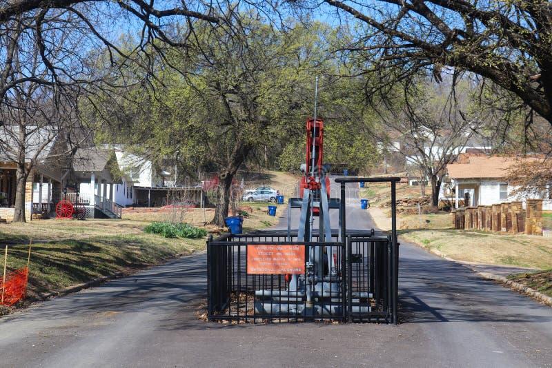 Poço de petróleo da rua principal dos mundos somente - bombeie o jaque no meio da rua em Barnsdall Oklahoma EUA 3 22 2018 fotografia de stock