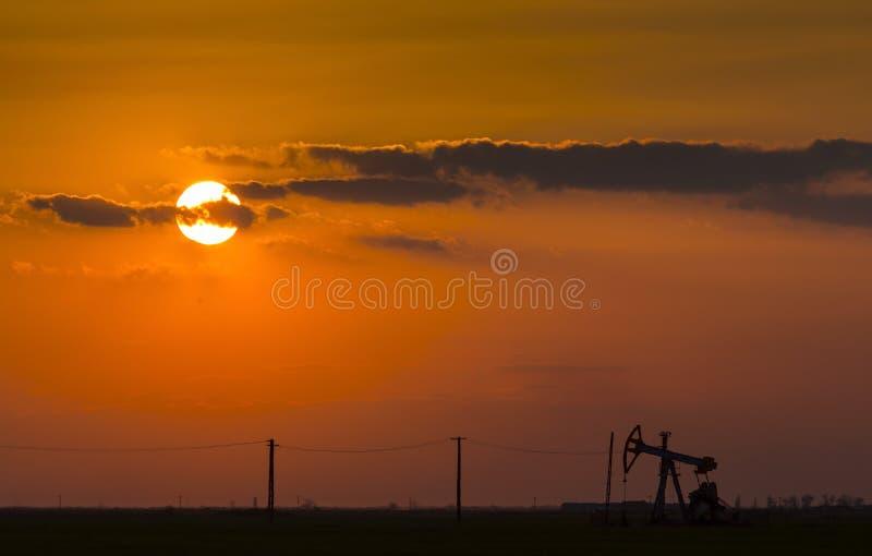 Poço de petróleo e gás de funcionamento perfilado no céu do por do sol imagem de stock