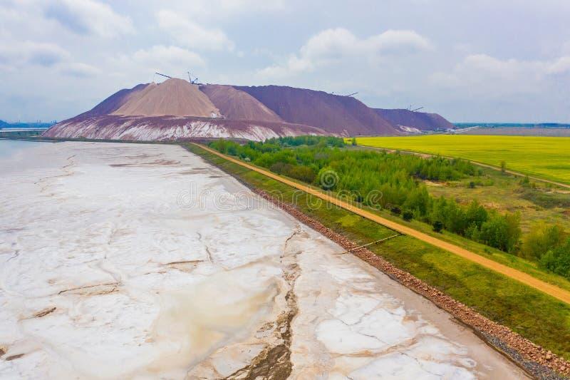 Poço de sal do potássio situado perto da terra de exploração agrícola e do reservatório do desperdício Paisagem industrial fotografia de stock