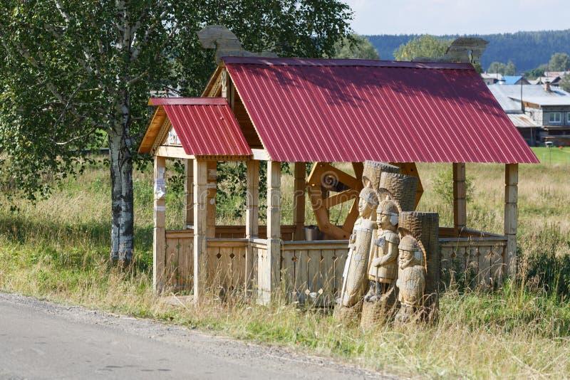 Poço e estátuas de madeira dos três heróis do russo foto de stock royalty free