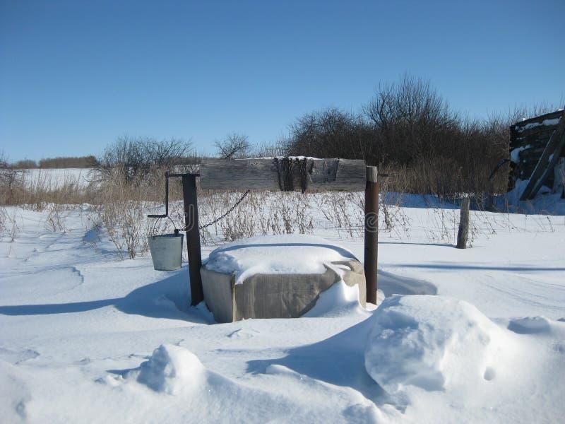 Poço velho No punho pendura uma cubeta Bucket em uma corrente, com que você pode obter a água Paisagem do inverno imagens de stock