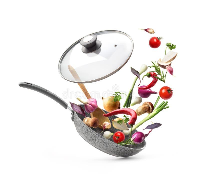 Poêle avec des légumes de couvercle et de vol, d'isolement sur le fond blanc photo stock