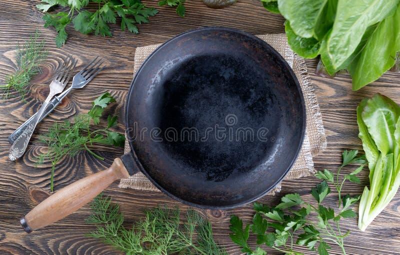 Poêle de fonte de vintage sur le fond en bois rustique avec des herbes image libre de droits