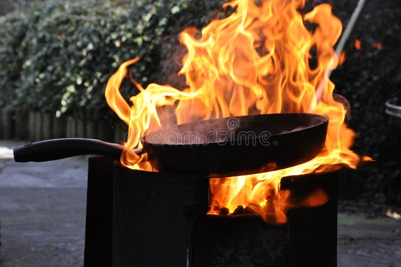 Poêle sur l'endroit ouvert du feu avec les flammes brûlantes images stock