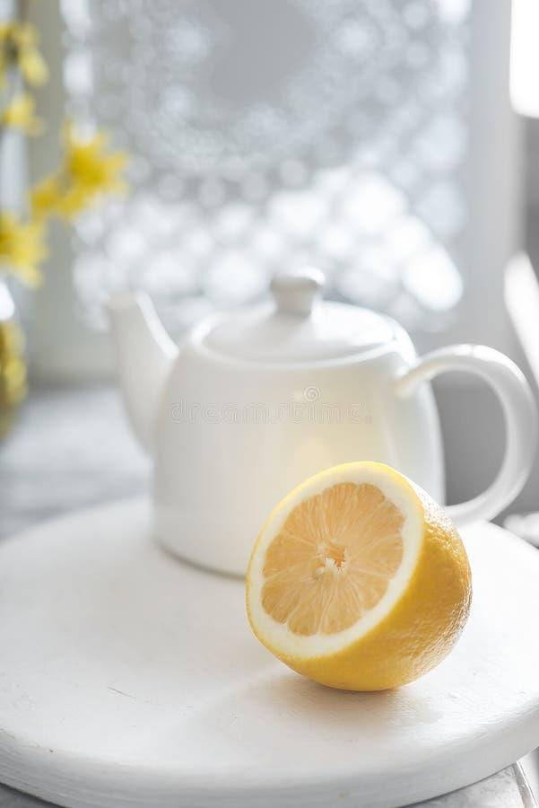 Połówka świeża cytryna i biały teapot jesteśmy na szarym tle zdjęcie royalty free