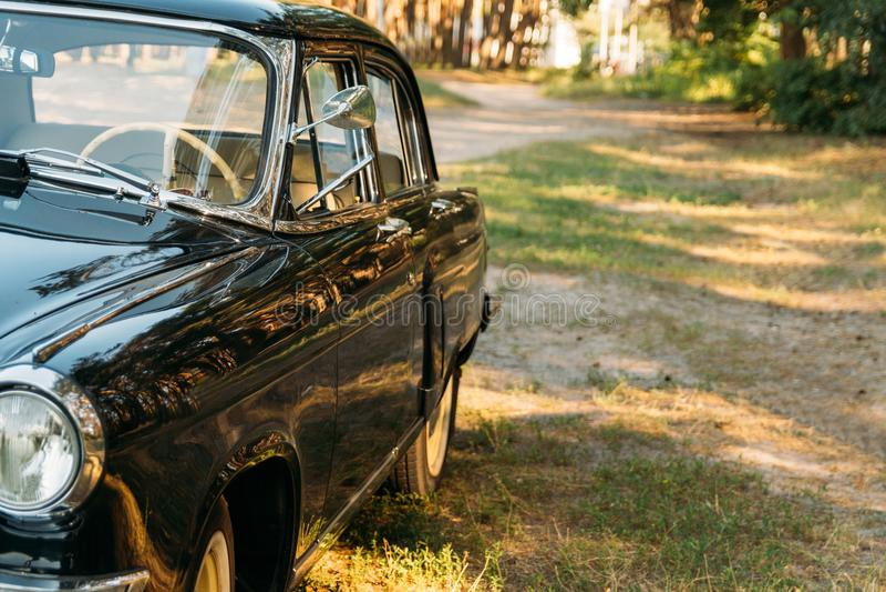 Połówka czerń, stara, rocznika samochód z świeceniem od słońca który stoi na polanie w dolinie na letnim dniu, fotografia royalty free