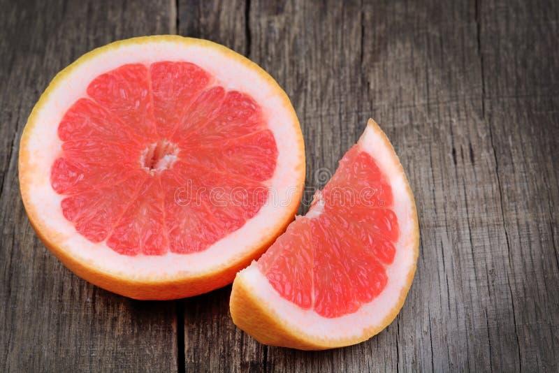 Połówka i kawałek czerwony grapefruitowy na drewno stole zdjęcia stock