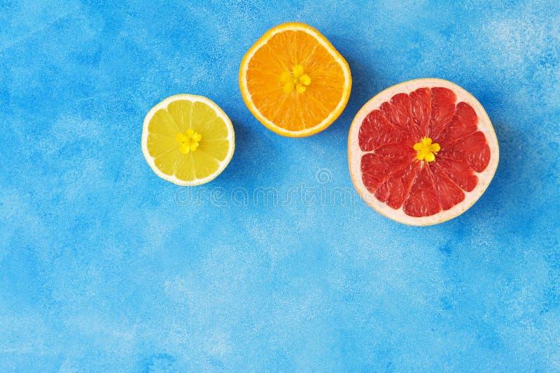 Połówka pomarańcze, cytryna i grapefruitowy na błękitnym tle cytrusa, Owoc dekorują z żółtymi kwiatami Odgórny widok, kopii przes zdjęcia royalty free