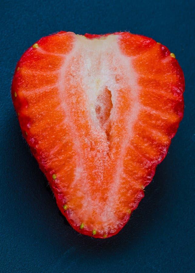 Połówka truskawka bez liści na czarnym tle zdjęcie stock