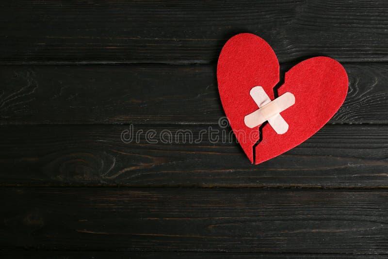 Połówki cięcie czuli serce łączącego z adhezyjnymi tynkami na ciemnym drewnianym tle, odgórny widok obrazy stock