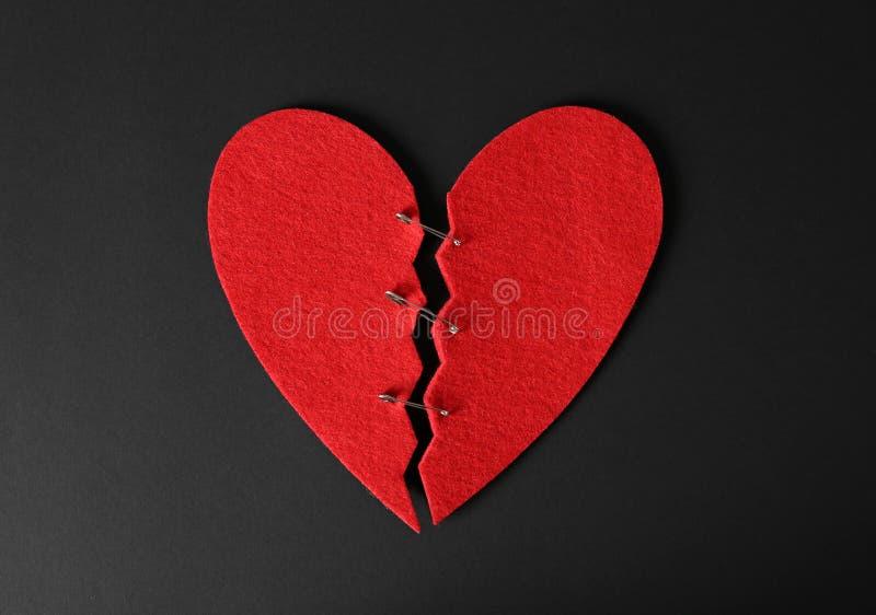 Połówki cięcie czuli serce łączącego z szpilkami na czarnym tle zdjęcie royalty free