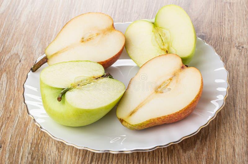 Połówki czerwona bonkreta, zielony jabłko w bielu talerzu na stole zdjęcia royalty free