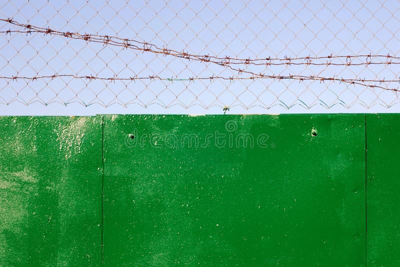 Połączenie i drut kolczasty na górze zieleni ogrodzenia fotografia royalty free
