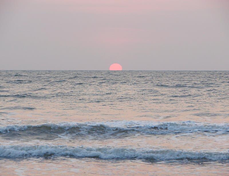 Położenia Czerwony słońce przy horyzontem nad morzem przy Payyambalam plażą, Kannur, Kerala, India obraz stock