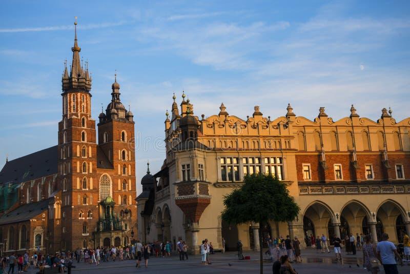 Położenia słońce na Mariacki bazylice i Sukiennym Hall na Targowym kwadracie w Krakow Polska zdjęcie stock