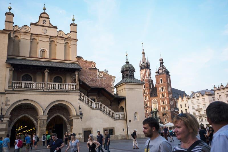 Położenia słońce na Mariacki bazylice i Sukiennym Hall na Targowym kwadracie w Krakow Polska obraz royalty free