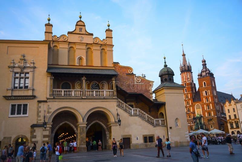 Położenia słońce na Mariacki bazylice i Sukiennym Hall na Targowym kwadracie w Krakow Polska fotografia stock