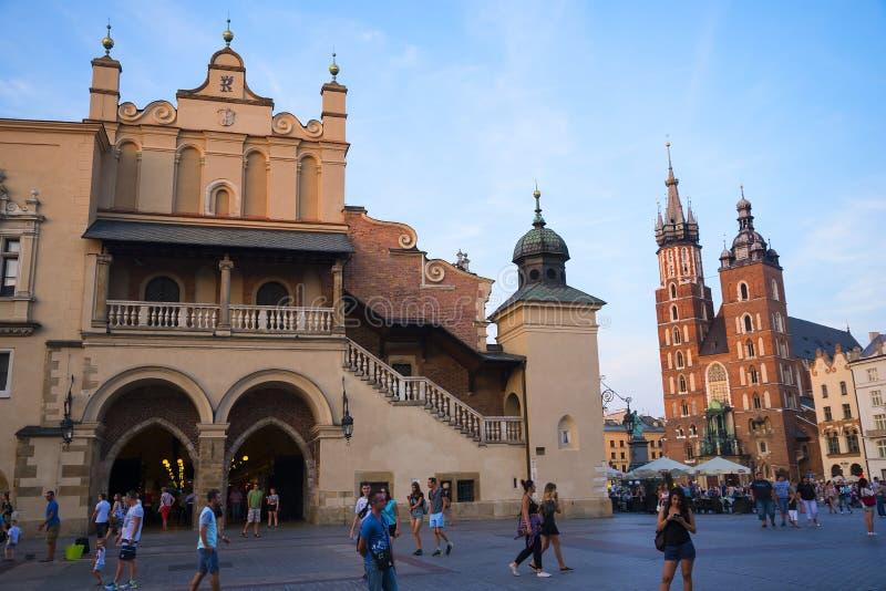 Położenia słońce na Mariacki bazylice i Sukiennym Hall na Targowym kwadracie w Krakow Polska obrazy royalty free