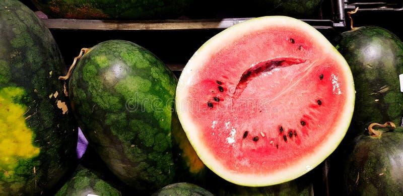 PoÅ'owa Å›wieżej arbuzy wkÅ'adana do czarnego plastikowego pojemnika na targu supermarketów lub na targu owocowym zdjęcia royalty free