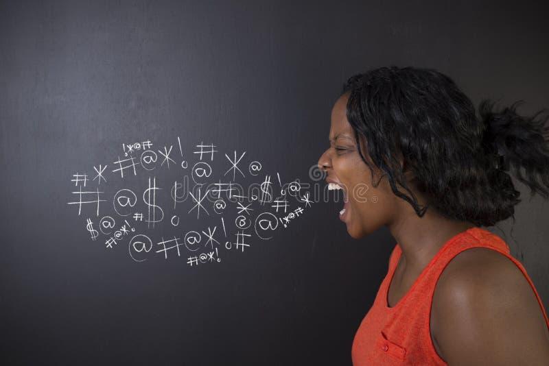Południe - afrykanin lub amerykanin afrykańskiego pochodzenia kobieta uczeń przeciw blackboard przysięganiu lub nauczyciel fotografia royalty free