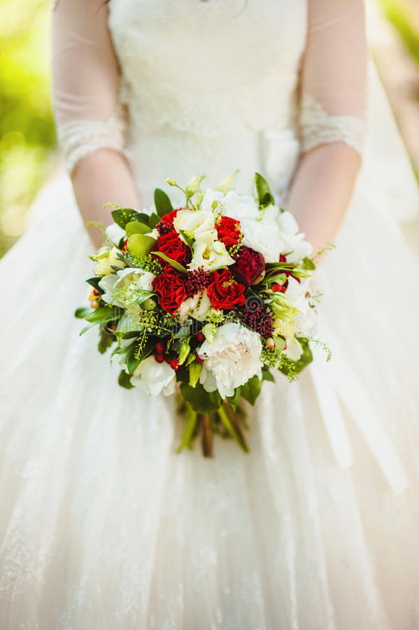 Poślubiać kwiat róż bukiet w pann młodych rękach z biel suknią na tle obrazy royalty free