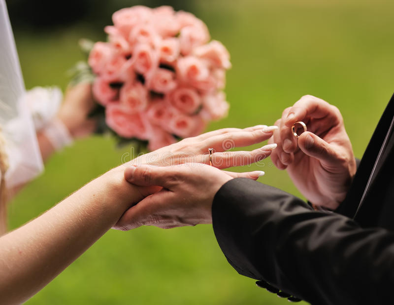 Poślubia ja.  Przygotowywa stawia pierścionek na palcu jego urocza żona. fotografia stock