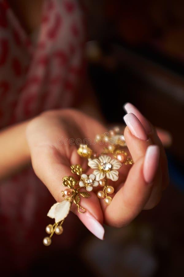 Poślubiający panny młodej trzyma hairpin mały w postaci kwiatu złotego hairpin w ręce dziewczyna fotografia royalty free