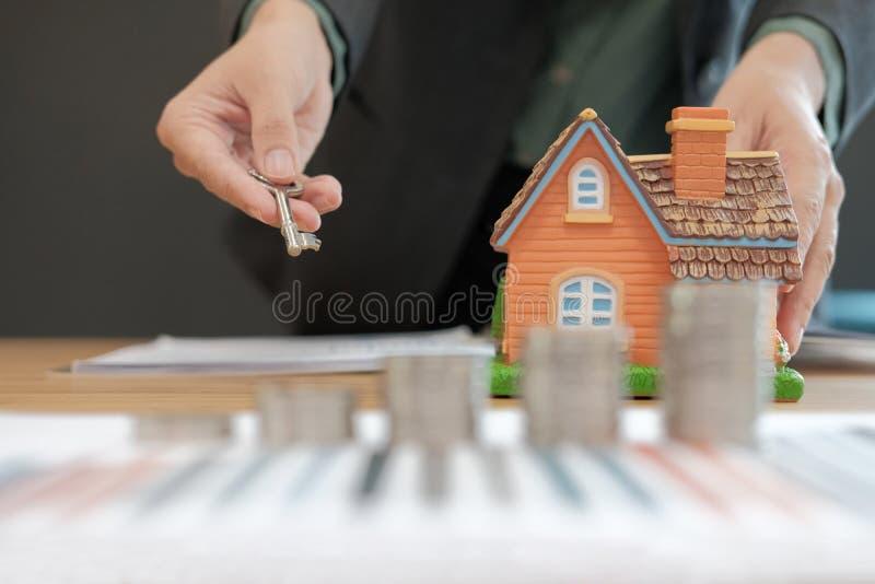 pośrednik handlu nieruchomościami agent z monety sterty domu kluczem & modelem oszczędzanie pieniądze f fotografia royalty free