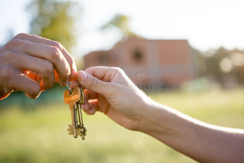 Pośrednik handlu nieruchomościami daje domowi kluczowego yo nowego właściciela fotografia royalty free