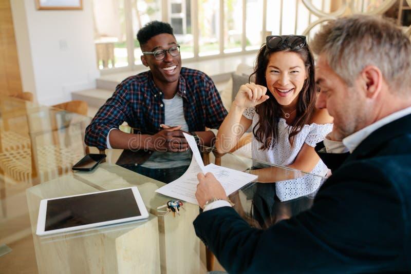 Pośrednik handlu nieruchomościami pokazuje terminy kontrakt szczęśliwa para obrazy stock