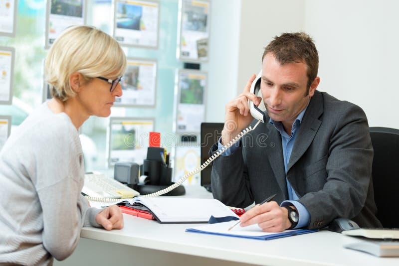 Pośrednik w handlu nieruchomościami w biurze z klientem opowiada na kablu naziemnym obrazy royalty free